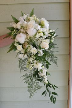 Beautiful bouquet, cascading in spring flowers including peony, ranunculus, lilacs, tulips, snowberry, freesia, sweet peas, ferns, and ruscus! White and green bouquet