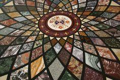 Mesa redonda de mármol con incrustaciones que se encuentran en los pasillos del Museo Vaticano. Cada pieza de mármol que representa la roseta es una variedad diferente. En el centro se puede ver los brazos de la Santa Sede.