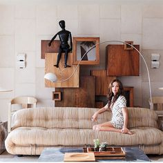 Kelly Wearstler's beach house has tile walls, a curved floor lamp, an organic shaped couch, wooden cube artwork and a maximalist style.