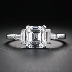 An almost square, and almost perfect, older emerald-cut diamond shines ice-white and gorgeous between a perpendicular pair of straight baguette diamonds in this exemplary diamond solitaire, masterfully hand crafted in platinum during the 1930s. Check out the belted back-to-back 'C' motifs on the side gallery.