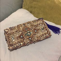 Anthro Beaded Clutch Absolutely gorgeous clutch from Anthropologie by Jasper & Jeera. Only used once at a wedding! Unfortunately a gem is missing as depicted above (pointing at it) but it is not very noticeable since there is so much detail going on! Beadwork is amazing and has a royal blue beaded tassel zipper! Please note there may be other beads missing but definitely nothing noticeable, I only found one other smaller missing bead. Anthropologie Bags Clutches & Wristlets