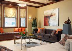 living room with light tan walls, orange accent pillows, dark wood trim (Benjamin Moore, Arizona Tan)