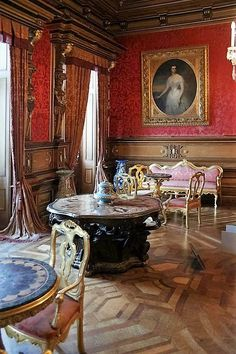 Red walled salon with antiques and a carved center table.