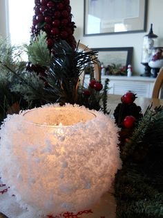 Even I could do this! Glass votives, spray adhesive, and artificial snowflakes from the craft store.