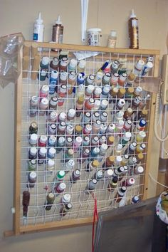 is that a child gate turned sideways?? kool!! paint storage idea #decoart  ---------------------------------------------------  I may just try framing some fencing I have. Gale K.