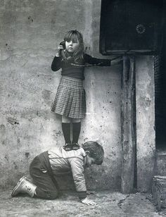 Young girl standing on boy to use telephone vintage