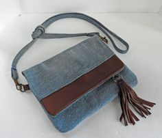 Travel light with just the essentials in this leather & denim purse. Made with soft supple brown leather, this pouch is sized to fit your keys, phone and a slim wallet with a little wiggle room. It features brown leather on the flap, leather handle loops and magnetic snap closure. The
