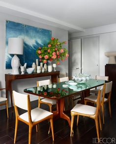 Modern yet classic dining space with ocean wave artwork, large arrangement of roses and reflective table