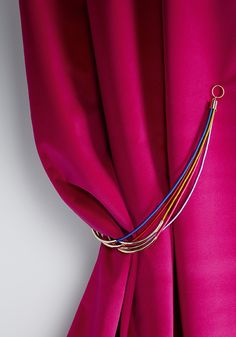 ILLUSTRA is a very decorative, ornamental tie-back. Sumptuous metal tubes are drawn into five elegant satin cords. An attractive black design, an elegant light shade and a fashionable multi-colored version open up individual styling possibilities. ILLUSTRA is very fashionable and looks like a fascinating piece of jewelry.