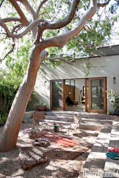 Rocks and stones suggest a Japanese garden in this courtyard retreat outside a Los Angeles house designed by Pamela Shamshiri for Commune. Amphitheater-style steps provide extra seating when the homeowners are having a party. Exterior sconces by Robert Lewis for Commune.