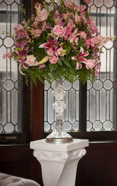 Elegant ceremony arrangement of Stargazer lilies, pink roses, stock, and alstromeria, on a tall, crystal tower, with iconic pedestal.