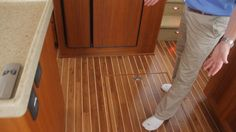 Nordic Tugs Nordic Tug 49: Teak and holly decking is used in the galley area providing an impressive traditional appearance. The hatch is under Captain Steve's foot.