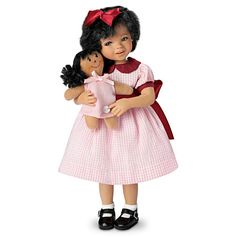 Handcrafted and hand-painted, she arrives in a pink-checked dress and with a FREE dolly of her own.