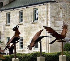 Cockatoo-sculptures-corten-steel,-1m-tall-birds,-stone-plinths
