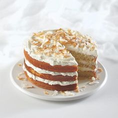 Just baked: Fluffy, sweet and oh-so-coco-nutty coconut cake. With frosting and batter flavored by Coconut Extract, this Ultimate Coconut Cake is heaven on a plate.