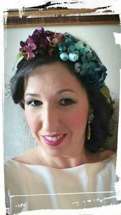 Media corona de flores en tonos azules, verdes y buganvilla.