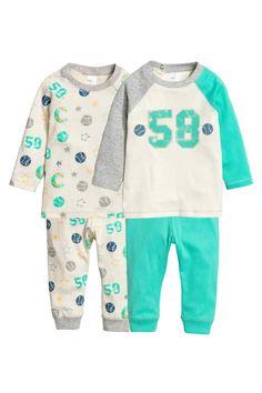 Set van 2 pyjama's: CONSCIOUS. Tweedelige tricot pyjama's van zacht, biologisch katoen. De top heeft een drukknoop op één van de schouders. De broek heeft elastiek in de taille en een boord onder aan de pijpen.