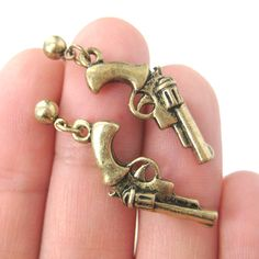 A pair of simple gun shaped dangle earrings in bronze!  Size: The earrings measure 3 cm long and comes with earring backs!  Material: Bronze Plated Tin Alloy  --- Handling time: - Please allow two to three business days for us to process your order - We will email you when we've sent it ...