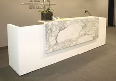 Custom reception desk.  Simple form and materials to emphasize it.  Not sure about ADA accessibility compliance- hard to tell from this photo...