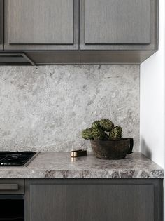 medium-grey kitchen cabinets with lighter grey marble counters and backsplash