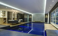 Luxe bouwkundig binnenzwembad, voorzien van een openhaard. | Zwembadrenovatie te Breda