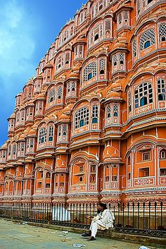 "Hawa Mahal (Hindi: हवा महल, translation: ""Palace of Winds"" or ""Palace of the Breeze""), is a palace in Jaipur, India. It was built in 1799 by Maharaja Sawai Pratap Singh, & designed by Lal Chand Ustad in the form of the crown of Krishna, the Hindu god. Its unique 5-storey exterior is also akin to the honeycomb of the beehive with its 953 small windows called jharokhas that are decorated with intricate latticework. The original intention of the lattice was to allow royal ladies to observe…"