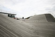The undulating deck of the Maritime Youth Center located in Amager Strand in Copenhagen invites rolling, climbing and exploration of the sloped surfaces.