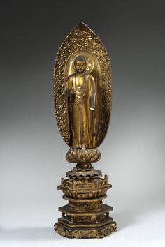 Piasa - Statuette de bouddha en bois laqué or debout sur le lotus devant une mandorle, posé sur un haut socle.  Japon, XVIIIe siècle  Hauteur : 89 cm