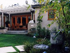 This outdoor dining area, built close to the house with custom BBQ, looks out to the Basalt fountain and pool area in this Modern Craftsman, Asian inspired landscape.