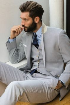 bearded brunette man, in light gray three piece suit, with light blue shirt, and a dark blue tie, sitting with a hand in his pocket