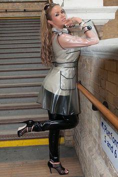 Blonde in transparent pvc raincoat black pvc pants and heels