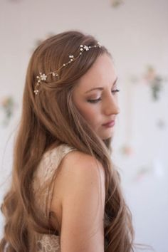 Hand-enameled brass flowers twirl together with delicately twisted crystal beads and freshwater pearls in this beautifully simple hair vine. Whether worn on its own or with a veil, the dainty piece adds a subtle amount of sparkle to any bridal look.