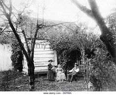 Homesteaders seated outside in garden surrounding house, probably Washington State - Stock Image