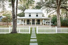 Renovated farmhouse with French doors, wrap around porch, gas lanterns and a metal roof. Doors and shutters are battleship gray. The picket fence makes it so charming! House Wrap Around Porch, House With Porch, Up House, House Doors, Modern Farmhouse, Farmhouse Front, Farmhouse Style, Texas Farmhouse, Farmhouse Windows