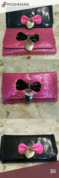 "Glitter Wallets Set of 2 Both walkets are NWT.  One pink with a black bow & one black with a pink bow.  Both have a silver heart charm dangling from the front.  Both have slots for your cards ir pictures, zippered pocket for change & 2 other open compartments for papets, etc.  Both measure 6""x3.5"".  Feel free to ask any questions before purchasing.   Thanks for shopping my closet! Bags Wallets"