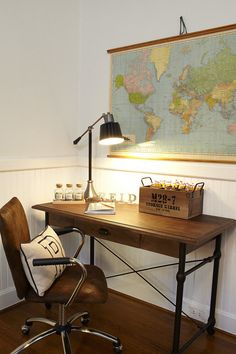 "Reid's desk space has an industrial vibe with a leather-and-chrome rolling chair and wooden desk. Vintage maps like the one shown here are plentiful on Etsy — just search ""Pull-down map,"" and you'll find an array of options. Photo: Nate Rehlander for Emily Hewett & Associates"
