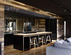 une cuisine élégante et noire avec un revêtement mural aspect bois