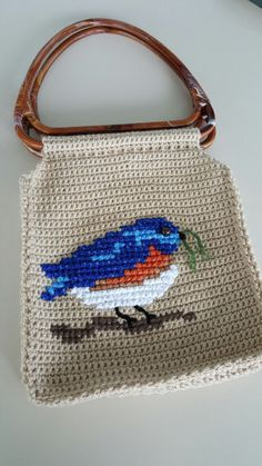 Yay! My crocheted tote is all finished with its cross stitch bird. I loved finding a use for the vintage handles discovered in my grandmother's craft stash. (She taught me to crochet when I was only ten or so.) This would make her smile. =)