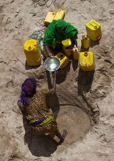 https://flic.kr/p/aKyXH6 | Nomadic people digging a well in Lasadacwo - Somaliland | Just outside of the village, in the bed of the dry river, some nomadic people had made a hole in the sand, and were collecting water they will bring back on donkeys. The people living in the village have their own wells, many thanks to NGO. I had a wonderful welcome in this village.  © Eric Lafforgue  www.ericlafforgue.com
