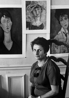 Artist Jeanne Modigliani with paintings of her mother, Jeanne Hubuterne, painted by her father Amedeo Modigliani. Paris, 1964. Photographed by Ralph Crane.