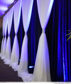 Wedding Backdrop with navy background and white/ivory gathered draping. Pink uplights in between the drapes. Sparkly bling thing to gather the drapes - shouldn't look too silver if possible.
