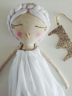 PRE ORDER white haired fairy doll, wearing white cotton dress star filled wings and gold sparkle crown. All removable.Will be shipped end of April.READY FOR HER FOREVER HOME.Handmade one of a kind heirloom cloth dollEach doll is hand dyed in tea  to create variations in skin tones and stuffed with eco friendly fibre stuffing. They are all made of cotton and clothed in new and recycled fabrics and findings.All seams are double stitched for extra strength. Each dol...
