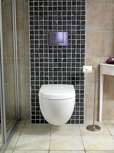 De beige flisene på badet brytes av svart mosaikk bak toalettet.