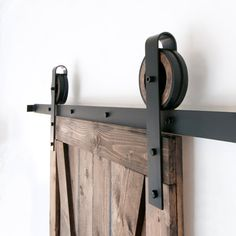 This is a BEAUTIFUL 6-8 foot rustic steel wide strap sliding barn door hardware set. Made in the USA from high quality steel (black) and wood. Includes: (1) 72-96 Track - 2 (2) Rollers - 5 1/2 Diameter, 1 1/2 Deep (4) Wall Spacers (2) Door Stops (1) Floor Guide To be used with opening