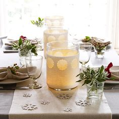 On smaller sections of felt, punch more scalloped-edge circles, and wrap felt around oversize glass vases. Insert candles for a soft, wintry white glow