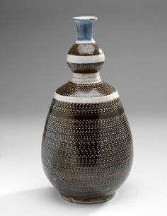 Tokkuri (decanter) of shoki-Imari type Hizen (Arita) ware  Shoki-Imari (early Imari) type, Hizen (Arita) ware  Porcelain, cobalt blue on the neck, with iron-brown and transparent glazes  Centimetres: 26.3 (height), 13.5 (outside diameter)  1660's  Early Modern; Edo  Area of Origin: Japan. ROM Images
