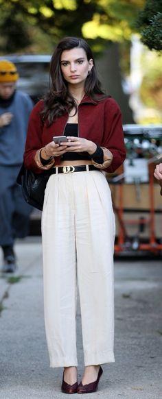 Emily Ratajkowski wears a crop top, high-waisted pants, a cropped jacket, and pumps
