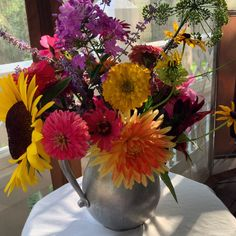 Aluminum pitcher filled with garden flowers.