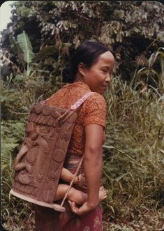 Vrouw met een kindje in een houten draagmand op Borneo, vermoedelijk in de Apo Kajan. 1980