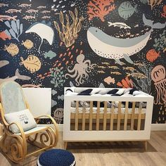 Nursery Decor With Dark And Moody Sea Life Wallpaper Dark and moody sea life wallpaper for a statement wall with a navy pillow and a cute whale one on the chair. Woodland Nursery Girl, Nautical Nursery Decor, Baby Room Decor, Dark Nursery, Nursery Neutral, Nursery Room, Kindergarten Wallpaper, Nursery Wallpaper, Kids Wallpaper